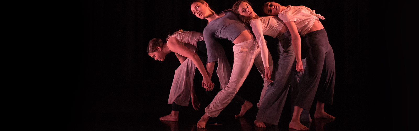 dancers in front of black backrop performing and leaning against one another
