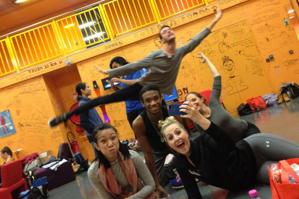 group of excited students posing an holding up student who is performing a dance pose