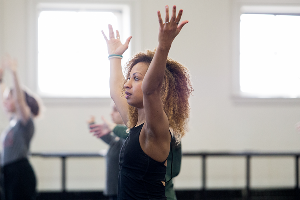 Photo of woman in dance class with her arms stretched above her head