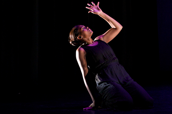 Photo of dancer on her knees, leaning back on one arm with the other in the air.